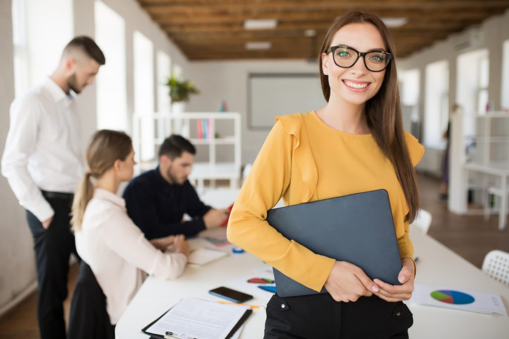 Young smiling business woman in eyeglasses happily looking in ca